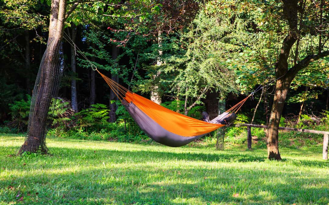 Ultimate Hammock Camping Guide Banner: a man resting in a purple and orange hammock between two trees.